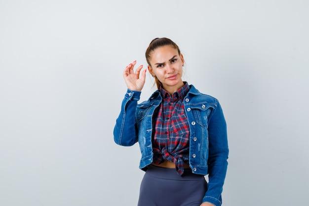 Молодая женщина показывает знак небольшого размера в клетчатой рубашке, куртке, штанах и выглядит серьезным, вид спереди.