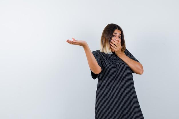 Giovane donna che mostra qualcosa tenendo la mano sulla bocca in abito polo e guardando stupito, vista frontale.