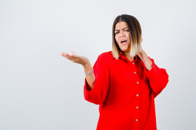 Giovane donna che mostra qualcosa mentre tiene la mano sul collo in camicia rossa oversize e sembra insoddisfatta, vista frontale.