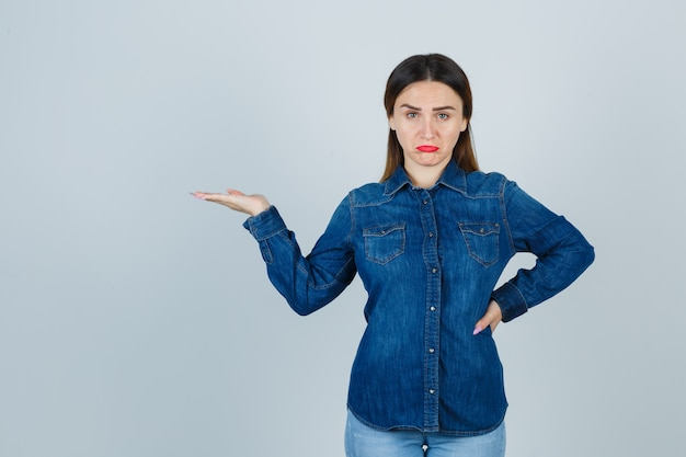 Young female showing something while keeping hand on hip in denim shirt and jeans and looking offended