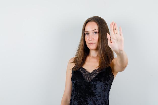 Молодая женщина показывает жест остановки в черной майке и выглядит уверенно.