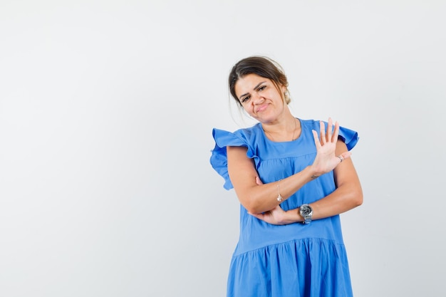 青いドレスで停止ジェスチャーを示し、イライラしている若い女性
