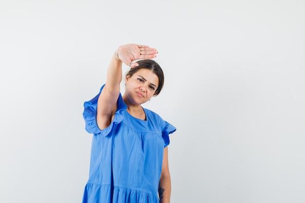 青いドレスで停止ジェスチャーを示し、自信を持って見える若い女性