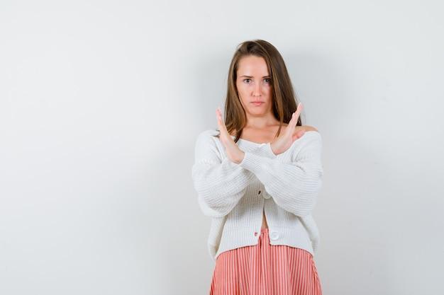 自信を持って孤立しているように見えるカーディガンとスカートで停止ジェスチャーを示す若い女性