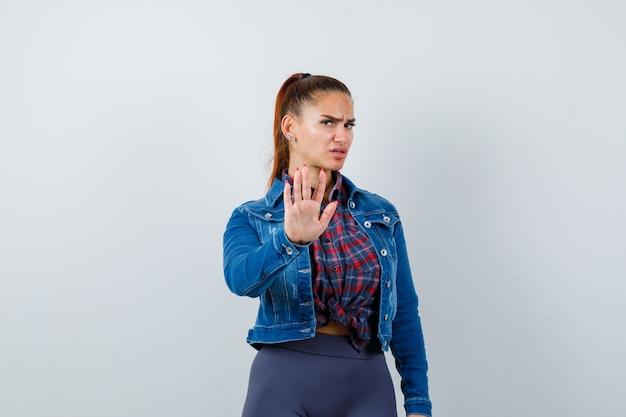 Молодая женщина показывает жест остановки в клетчатой рубашке, куртке, штанах и выглядит серьезным, вид спереди.