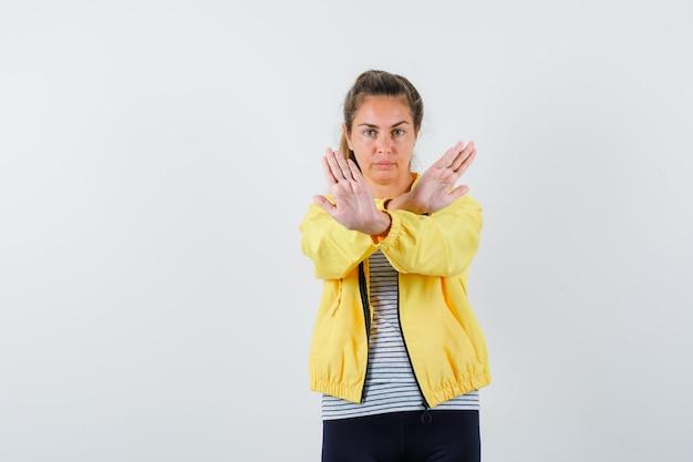 ジャケット、tシャツ、自信を持って、正面図で停止ジェスチャーを示す若い女性。