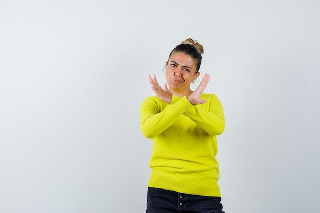 セーター、デニムスカートで停止ジェスチャーを示し、自信を持って見える若い女性