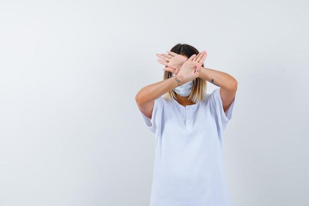 젊은 여성 t- 셔츠, 마스크에 중지 제스처를 표시 하 고 심각한, 전면보기를 찾고.