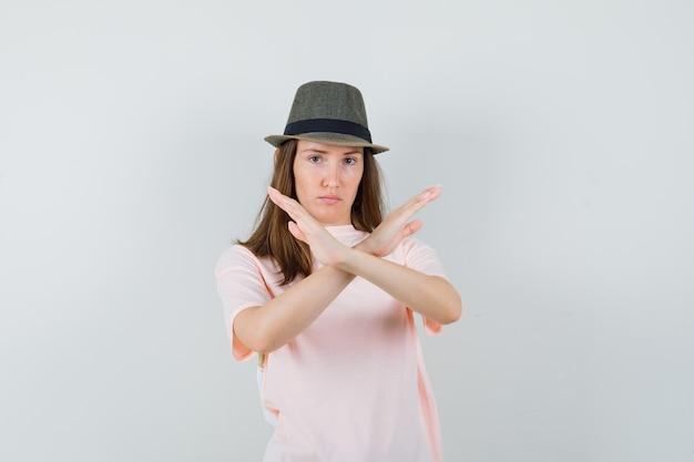 Giovane femmina che mostra il gesto di arresto in maglietta rosa, cappello e sguardo serio, vista frontale.