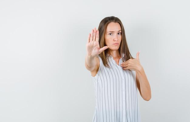 「私?」を身振りで示す間、停止ジェスチャーを示す若い女性。 tシャツを着て真面目な顔つき、正面図。