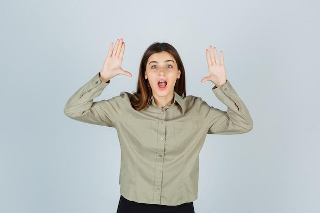 シャツ、スカート、ショックを受けた、正面図で降伏ジェスチャーを示す若い女性。