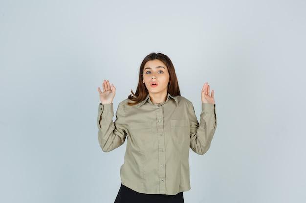 Giovane femmina che mostra gesto di resa in camicia, gonna e sguardo spaventato