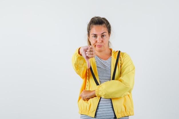 Giovane femmina che mostra il pollice verso il basso in giacca, t-shirt e guardando fiducioso. vista frontale.