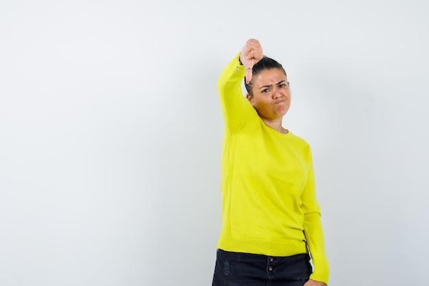 Giovane donna che mostra il pollice in giù in maglione, gonna di jeans e sembra malinconica