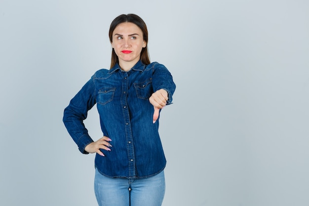 Young female showing thumb down while keeping hand on hip in denim shirt and jeans and looking displeased