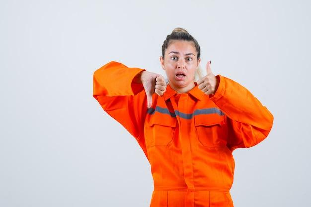 労働者の制服を着て上下に親指を示し、混乱しているように見える若い女性、正面図。