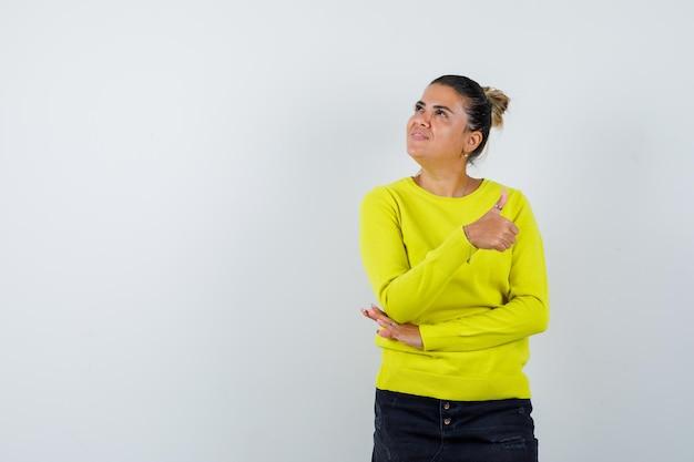 セーター、デニムのスカートに親指を立てて自信を持って見える若い女性