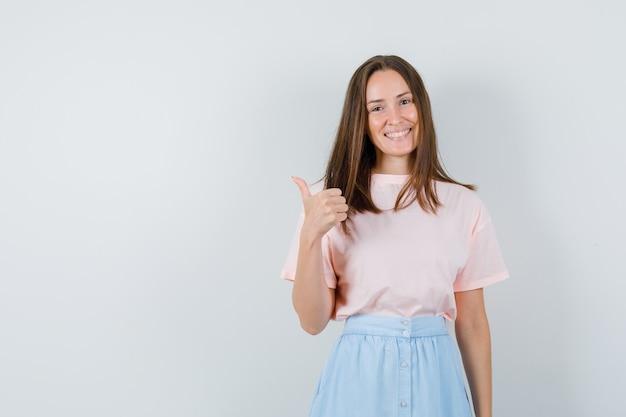 Молодая женщина показывает палец вверх в футболке, юбке и выглядит веселым, вид спереди.