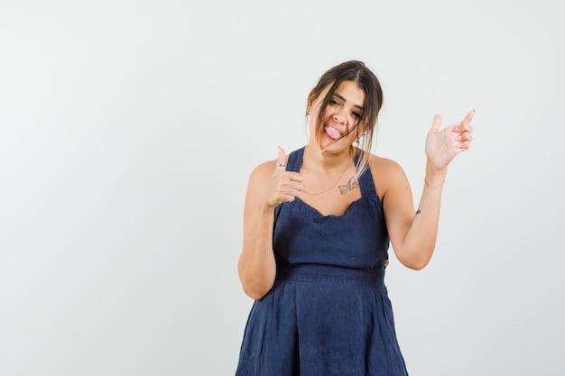親指を上に向けて、向こう側を指して、紺色のドレスで舌を突き出している若い女性