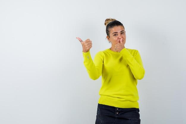 Giovane donna che mostra pollice in su in maglione, gonna di jeans e sembra sicura