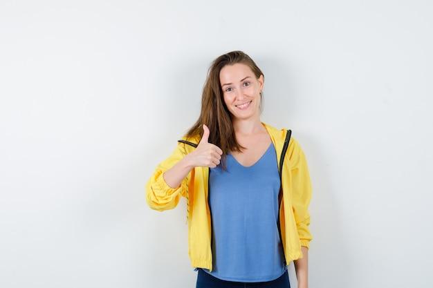 Giovane femmina che mostra pollice in su in maglietta, giacca e sembra allegra. vista frontale.