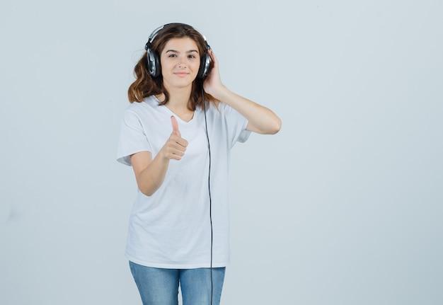 白いtシャツ、ジーンズ、幸せそうに見えるヘッドフォンで音楽を楽しみながら親指を表示する若い女性。正面図。
