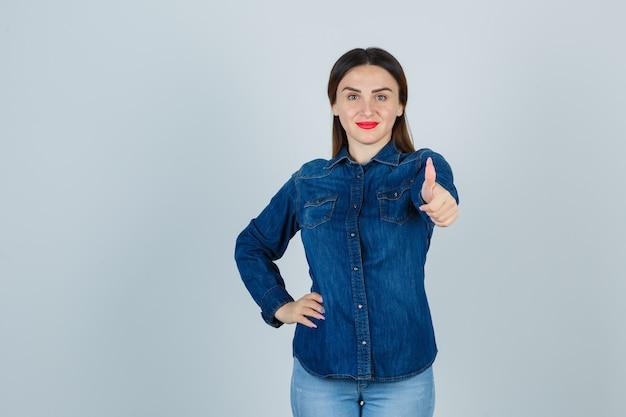 デニムシャツとジーンズで腰に手を保ちながら親指を上げて喜んでいる若い女性