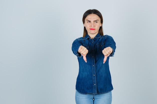 Young female showing thumbs down in denim shirt and jeans and looking displeased