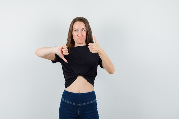 Молодая женщина показывает большие пальцы руки вверх и вниз в черной блузке, брюках и выглядит нерешительно