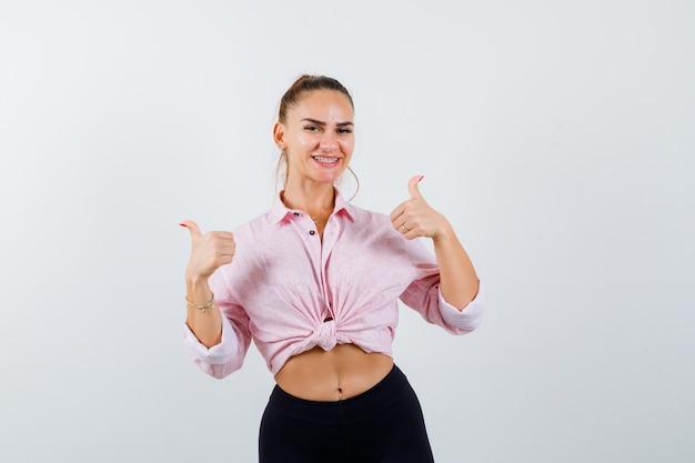カジュアルなシャツに親指を立てて幸せそうに見える若い女性。正面図。