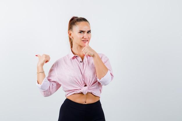 Молодая женщина показывает палец вверх в повседневной рубашке, штанах и выглядит радостным, вид спереди.