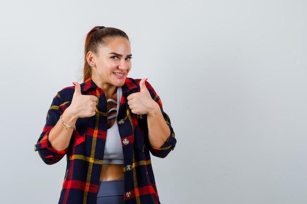 クロップトップ、市松模様のシャツに親指を立てて幸せそうに見える若い女性。正面図。