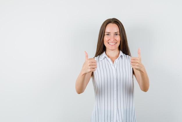 Tシャツに親指を立てて陽気に見える若い女性、正面図。