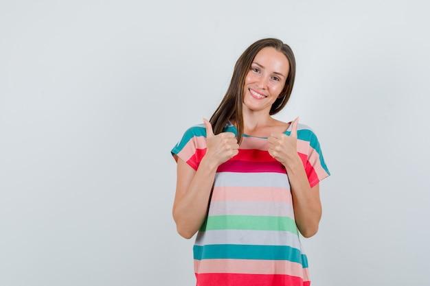 Tシャツに親指を立てて幸せそうに見える若い女性。正面図。