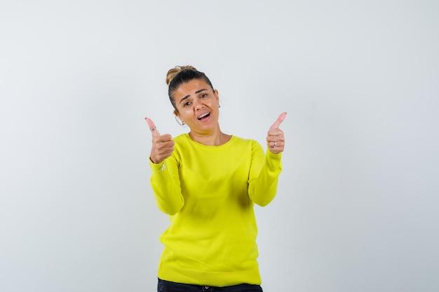 Giovane donna che mostra i pollici in maglione, gonna di jeans e sembra carina