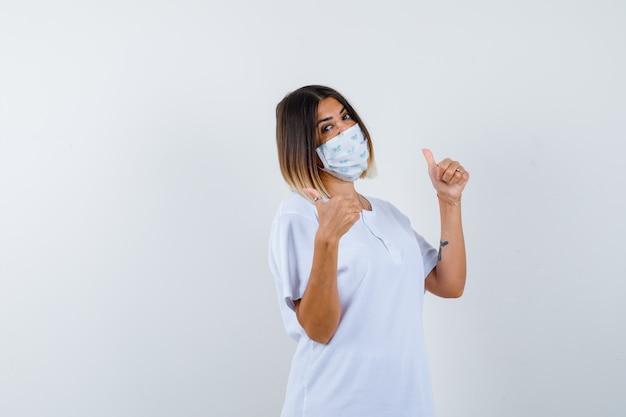 Giovane donna che mostra i pollici in su in t-shirt, maschera e guardando fiducioso, vista frontale.
