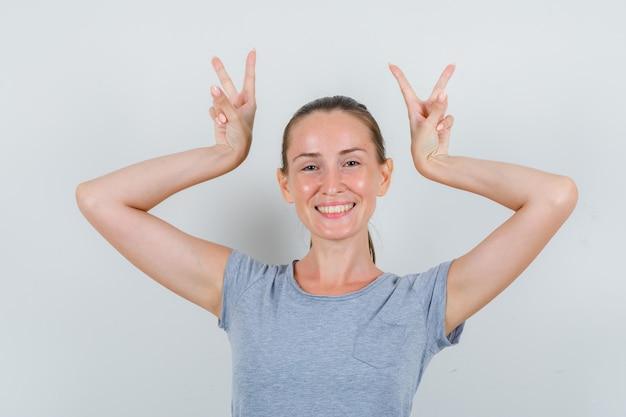 Giovane femmina che mostra il segno di v come le corna in maglietta grigia e che sembra divertente. vista frontale.
