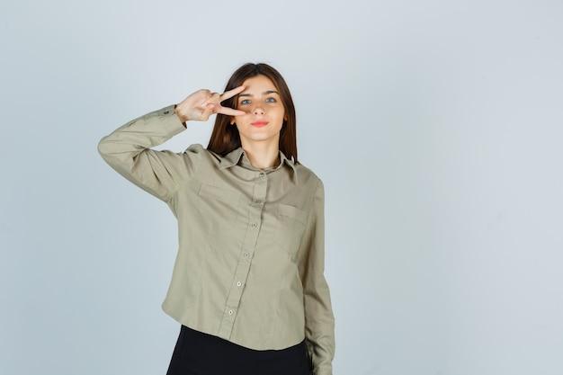 シャツ、スカート、自信を持って、正面図で目の近くにvサインを示す若い女性。
