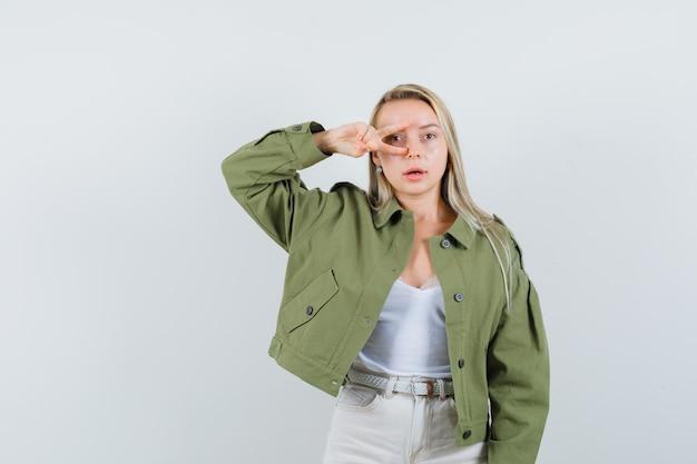 ジャケット、ブラウス、正面図でvサインオーバーアイを示す若い女性。