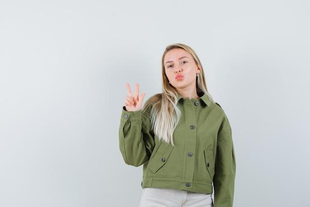 緑のジャケット、ジーンズ、正面図で唇をふくれっ面しながらvサインを示す若い女性。