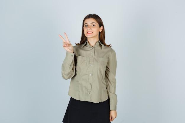 Giovane femmina che mostra il gesto di vittoria in camicia, gonna e sguardo allegro
