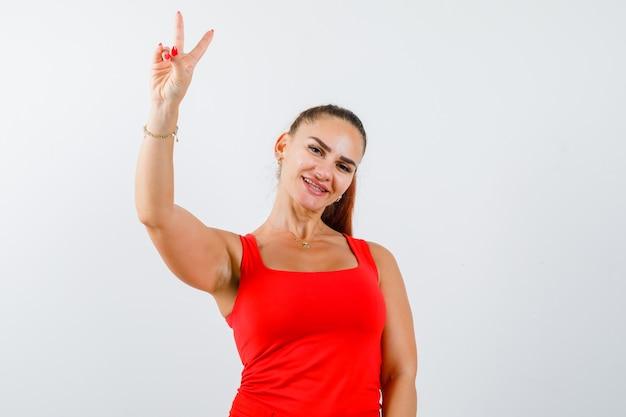 赤いタンクトップ、ズボン、至福の正面図で勝利のサインを示す若い女性。