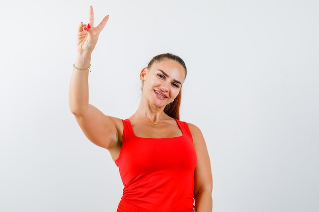 Young female showing victory sign in red tank top, pants and looking blissful , front view.