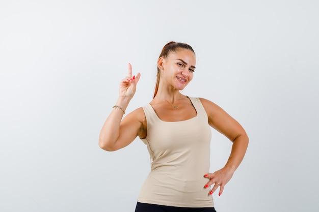 Giovane donna che mostra il segno di vittoria tenendo la mano sul fianco in canottiera beige e guardando felice, vista frontale.