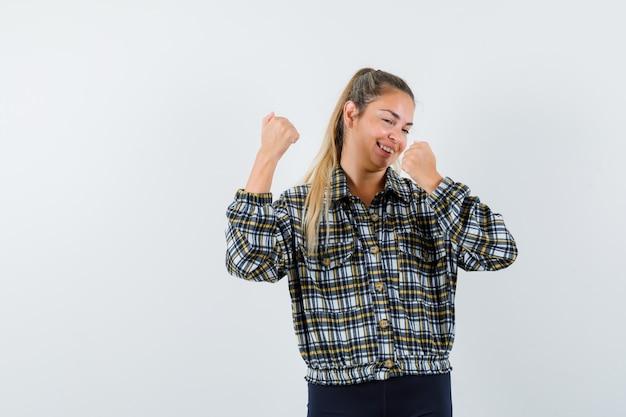체크 셔츠에 우승자 제스처를 보여주는 젊은 여성 운이 좋은 찾고. 전면보기.