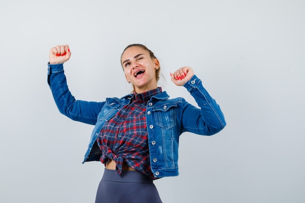 市松模様のシャツ、ジャケット、パンツで勝者のジェスチャーを示し、至福に見える若い女性。正面図。