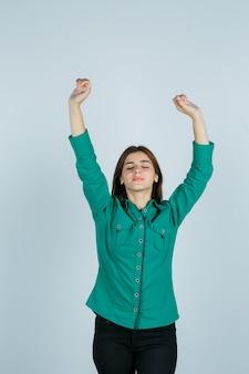 緑のシャツ、ズボン、陽気に見える、正面図で勝者のジェスチャーを示す若い女性。