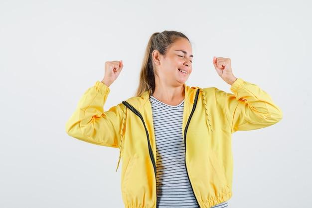 재킷, t- 셔츠에 우승자 제스처를 보여주는 젊은 여성과 행복을 찾고. 전면보기.