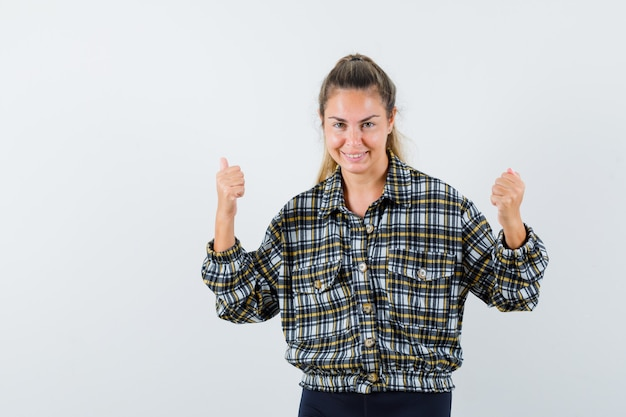 젊은 여성 셔츠, 반바지에 우승자 제스처를 보여주는 쾌활한, 전면보기.