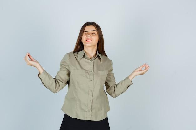 Giovane donna che mostra gesto di yoga mentre sbatte le palpebre in camicia, gonna e sembra pensierosa. vista frontale.